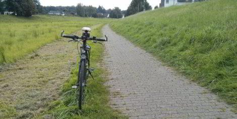 Die Reifen meines Fahrrades stehen genau auf der Begrenzungskante der Pflastersteine.