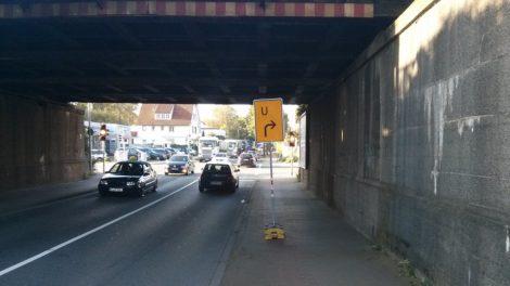 Umleitungsschild mitten auf dem benutzungspflichtigen Radweg in der dunklen Unterführung.